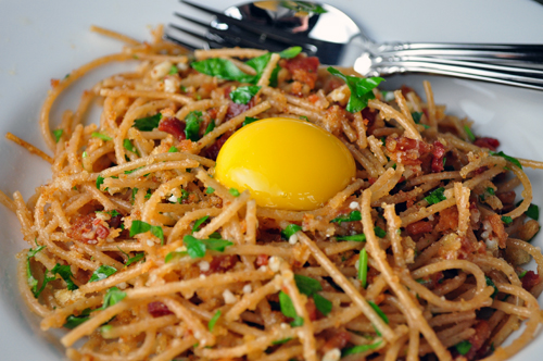 spaghetti carbonara with toasted garlic breadcrumbs served with a raw egg yolk on top