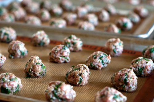 pork meatballs uncooked on baking sheets